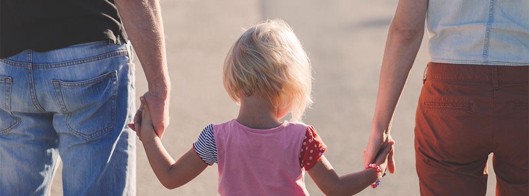 parents qui donnent la main à une petite fille