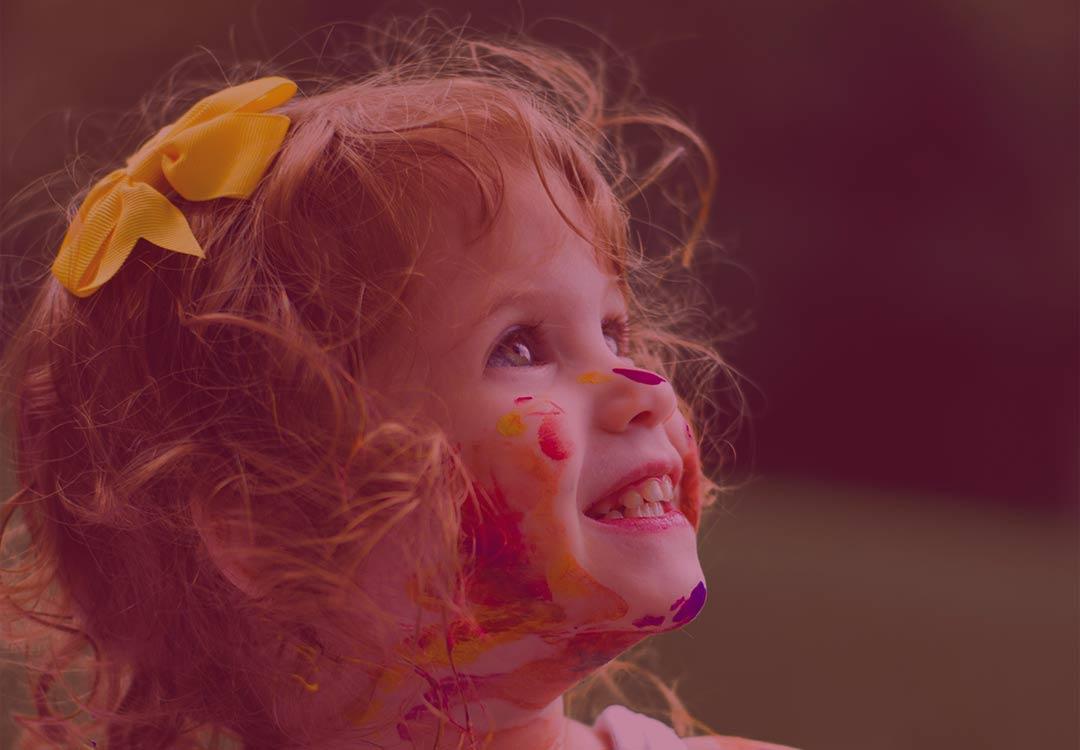 petite fille blonde barbouillee de peinture toute souriante